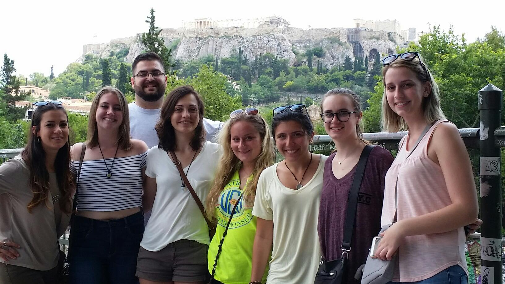 group of students pose before the Athenian Acropolis--in the distance