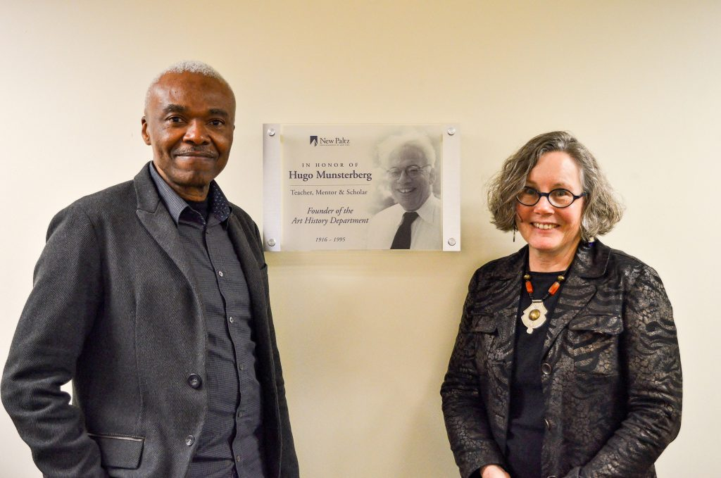 Speakers for the AHA 2017 Symposium, Studies in African Art, pose with the plaque honoring the founder of the Art History department, Dr. Hugo Munsterberg, installed in the Art History Visual Resources Study Room, SAB 106C. Photo by Katie Gantley