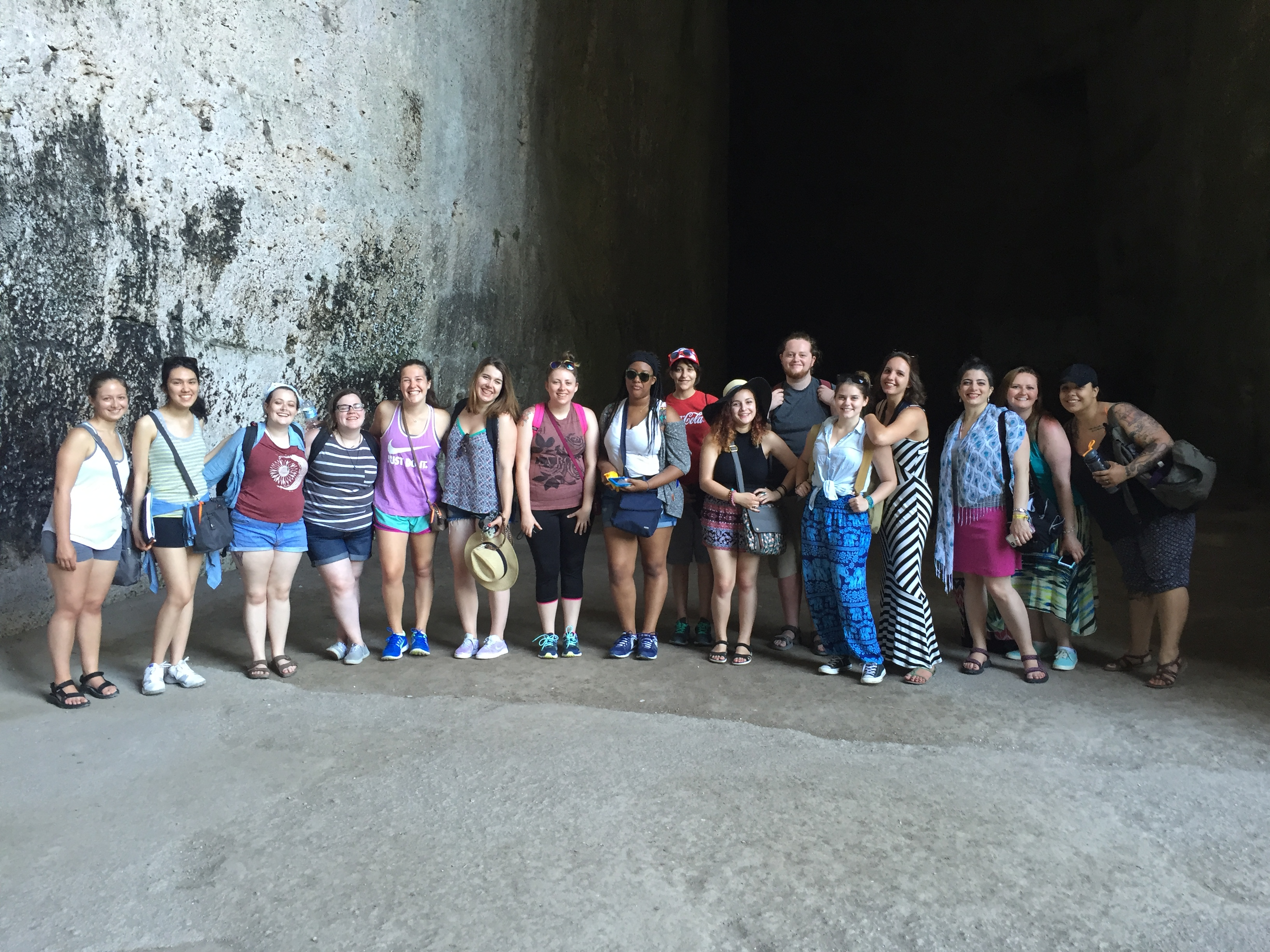 Group photo of 16 students from On-Site Studies in Art History Abroad Summer 2016 program, The Greeks in Ancient Italy. The students are posed at the mouth of an ancient rock quarry cave site in Syracuse, known as the 'Ear of Dionysios.' The cave is known for its exceptional acoustics: noises echo, but repeat only once. Ancient tyrants eavesdropped on prisoners they held captive here.