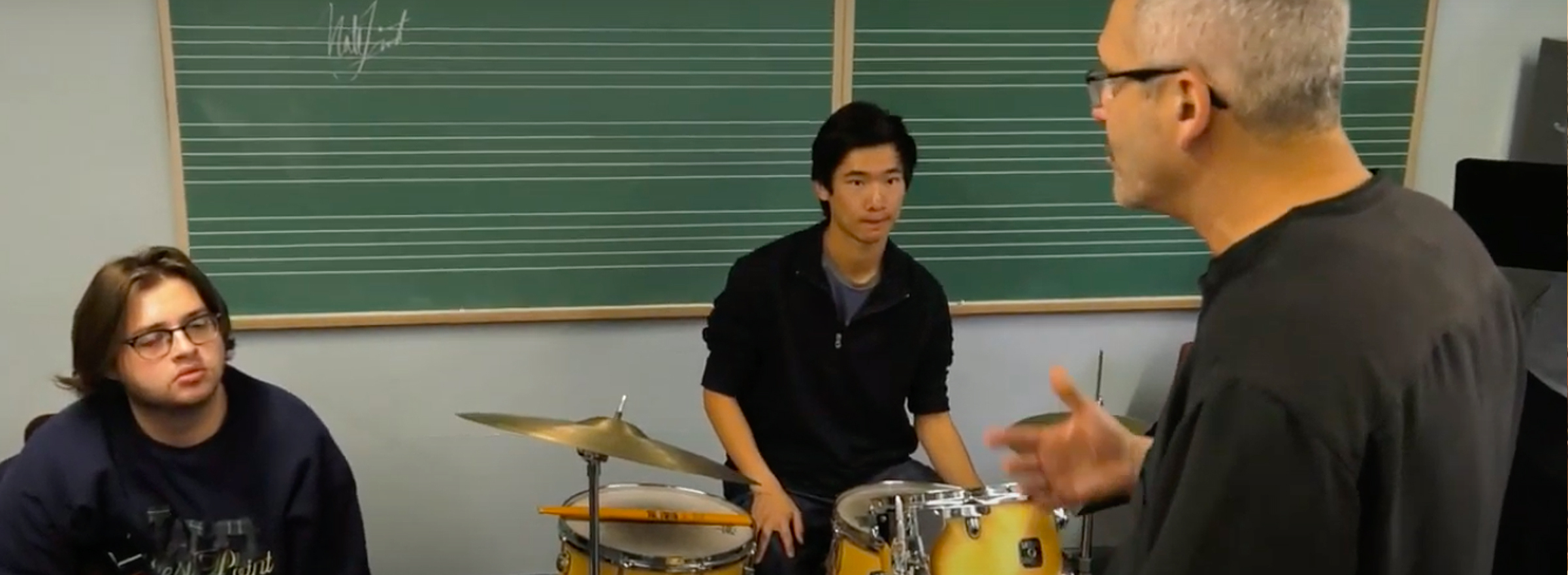 students in a classroom with a drum set