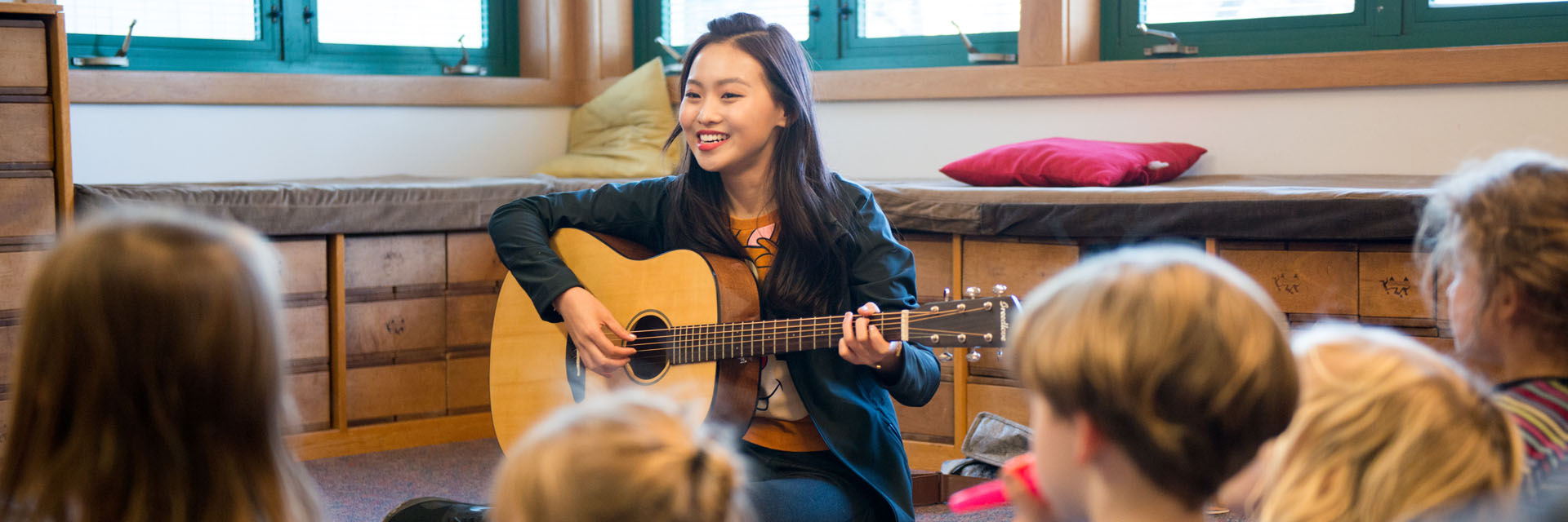 Student playing guitar to elementary children