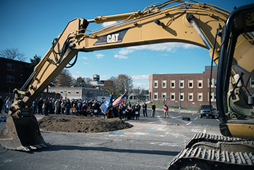 CAT fronthoe in foreground of Ground Breaking ceremony