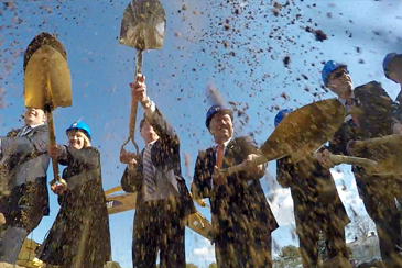 Participants at the Ground breaking ceremony throw dirt in the air with shovels