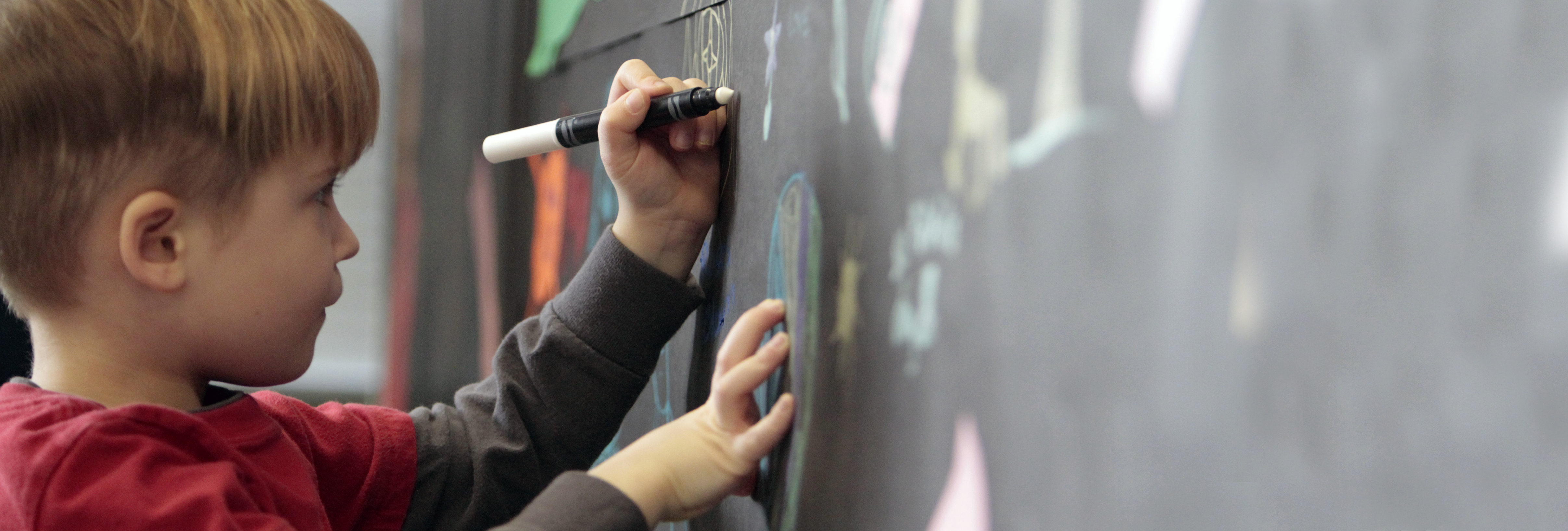 child drawing pictures on a blackboard