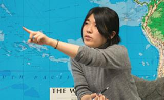 Student pointing to world map